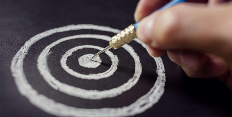 Businessman target for success holding dart on blackboard