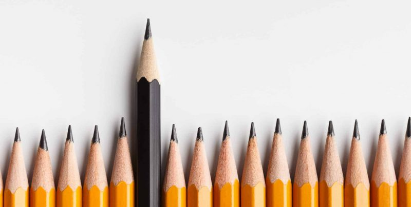 Concept for creativity and solution. One black pencil protruding out of line with similar ones, panorama