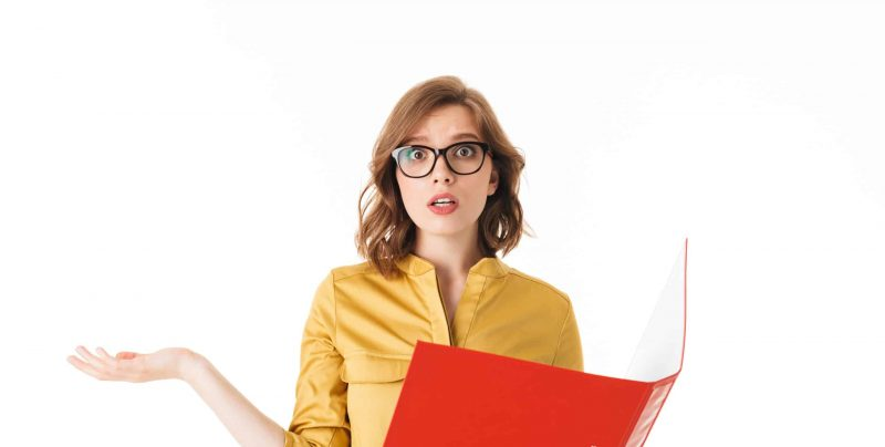 Portrait of young lady in eyeglasses standing with open red folder and amazedly looking in camera on white background isolated
